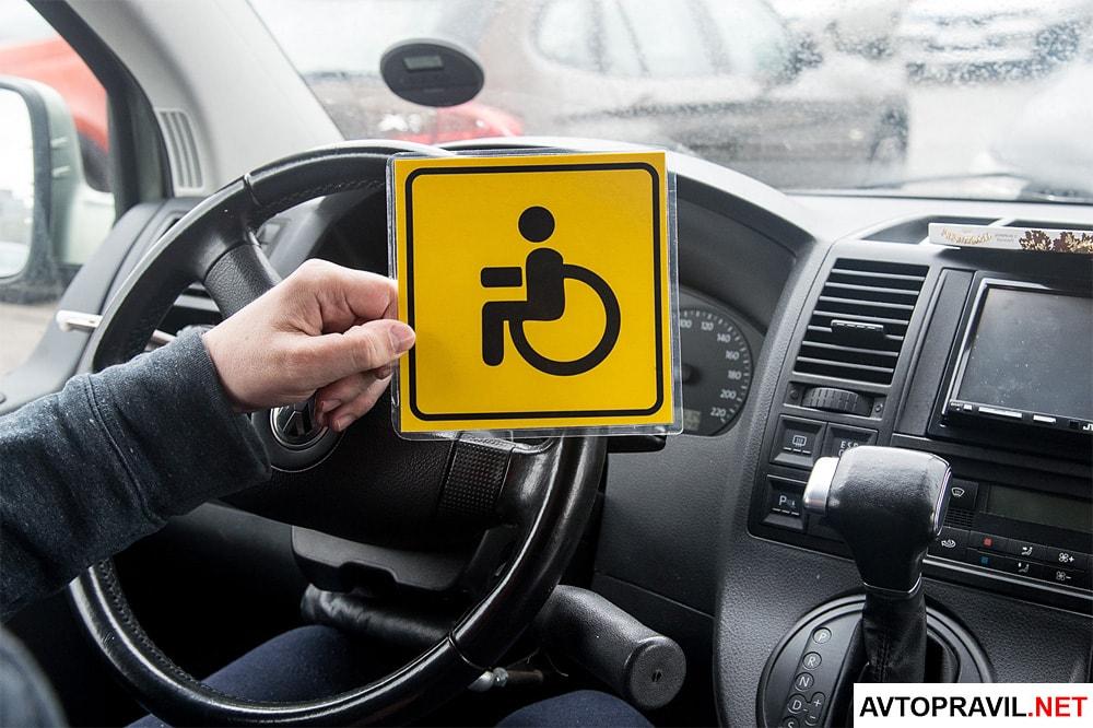 Мужчина держащий в руках наклейку инвалид за рулем