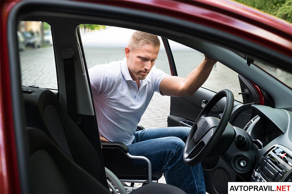 мужчина пересаживается с инвалидного кресла в машину