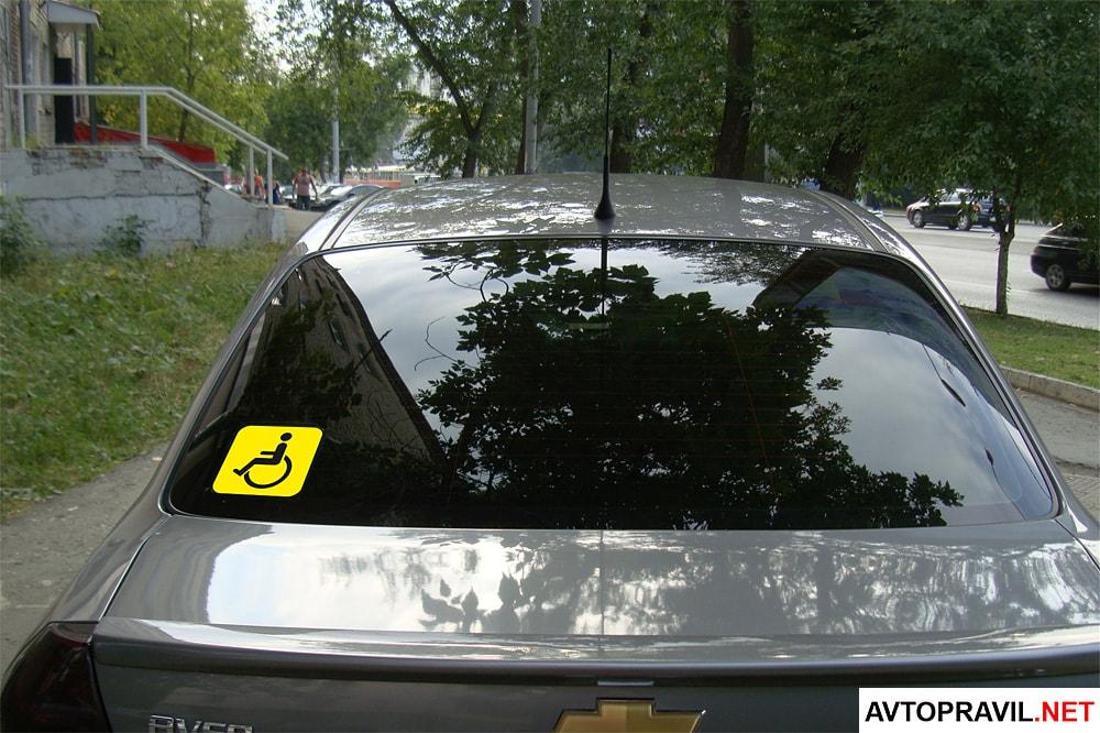 Наклейка инвалид за рулем на заднем стекле машины