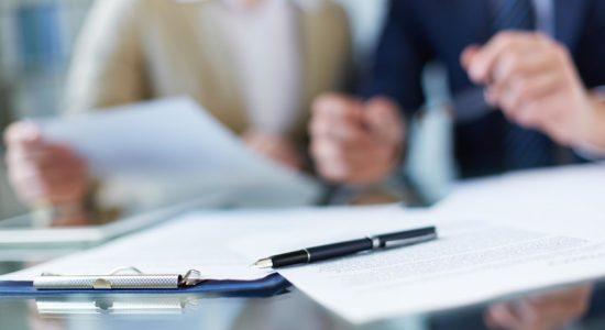 2 человека за столом оформляют документы