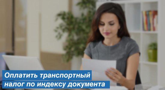 девушка держит в руках документ и сидит возле компьютера
