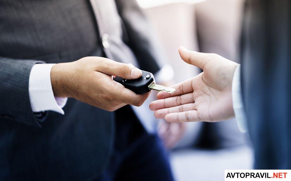 Мужчина передающий ключи от автомобиля другому мужчине
