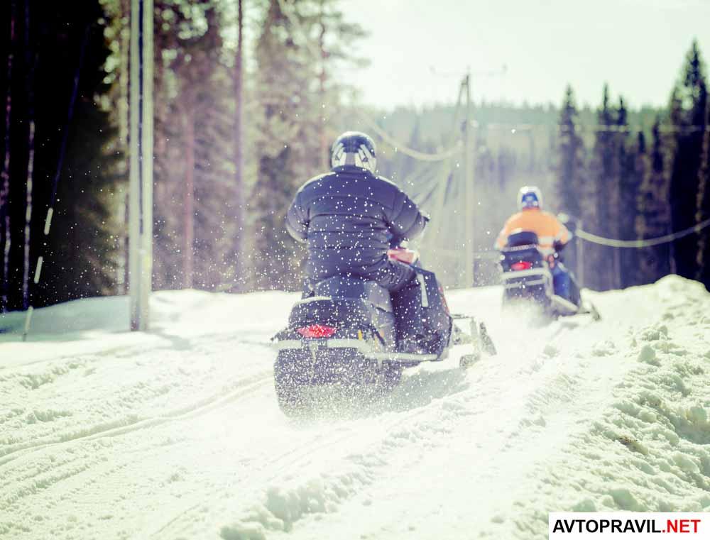 2 человека, которые едут на снегоходах