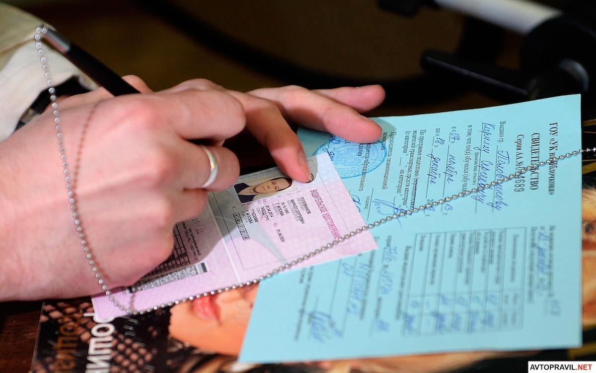 Девушка пишащая ручкой на водительском удостоверении