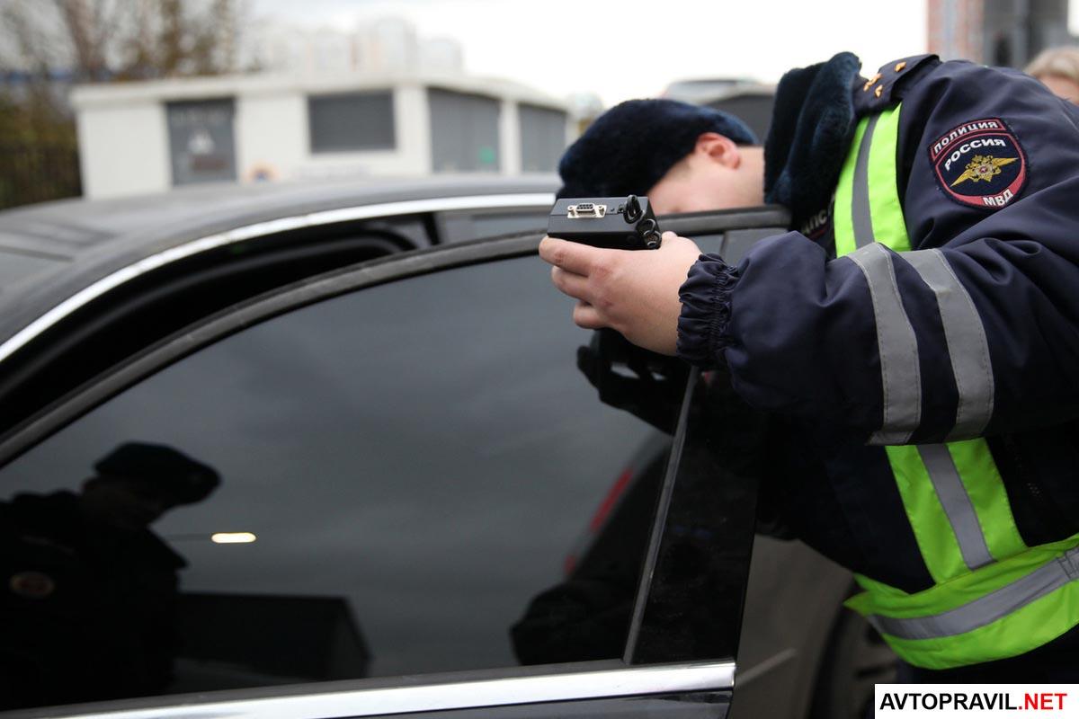 Инспектор ГИБДД, производящий проверку светопропускаемости стекол