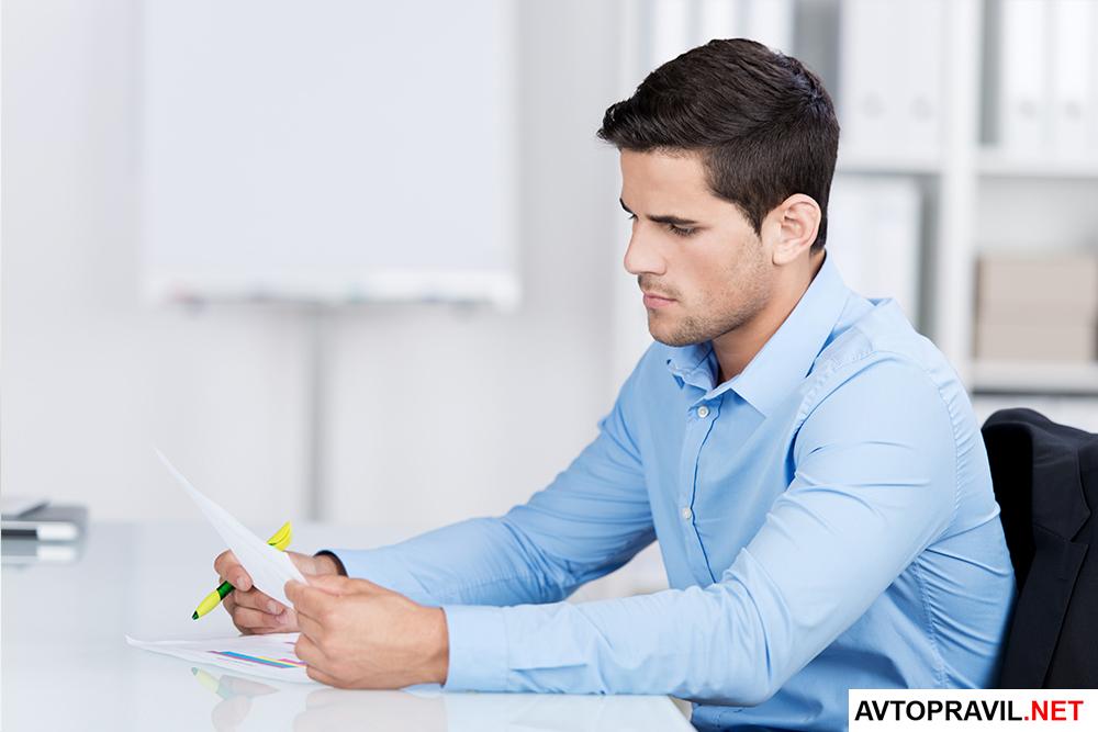 Человек, читающий документы за столом