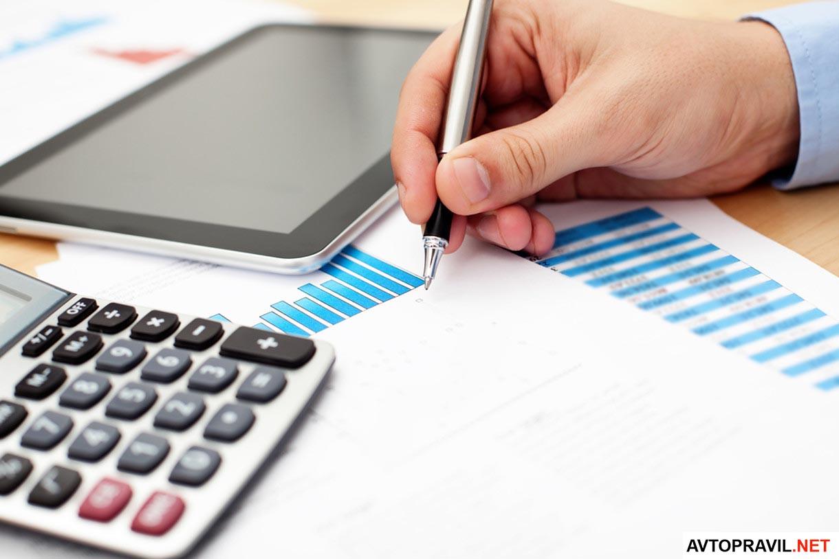 ручка в руках и калькулятор на столе на бумагах
