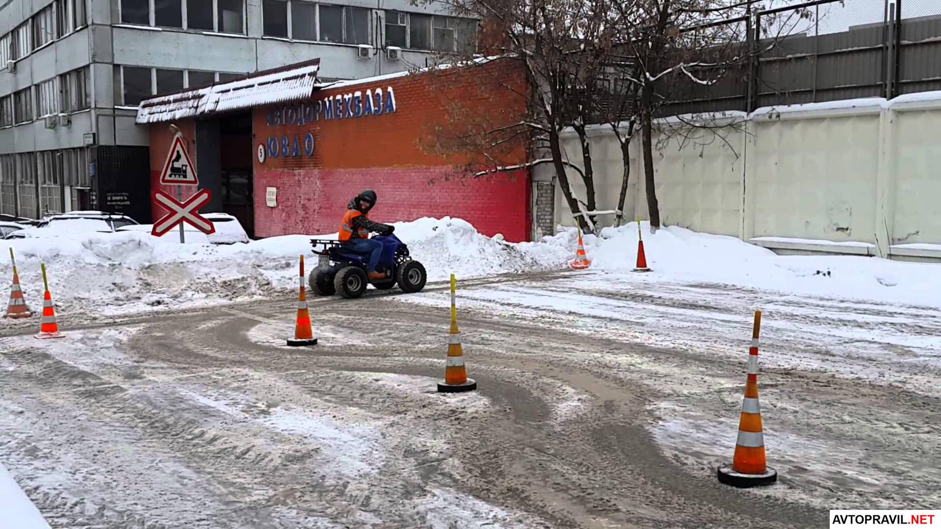 Человек на автодроме, который едет на квадроцикле