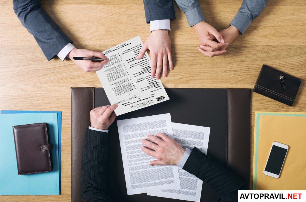 люди оформляют документ на столе
