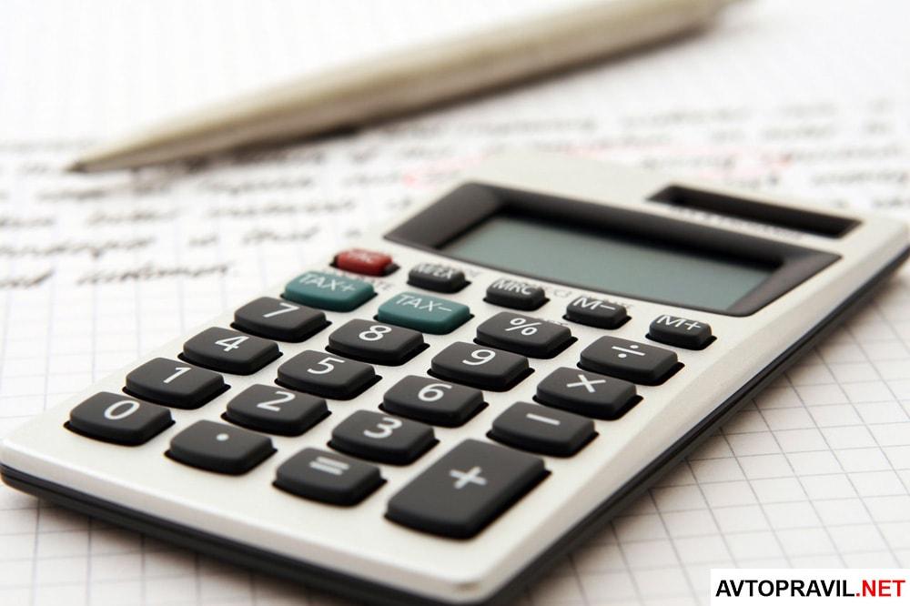 Калькулятор с ручкой, лежащие на тетрадном листе