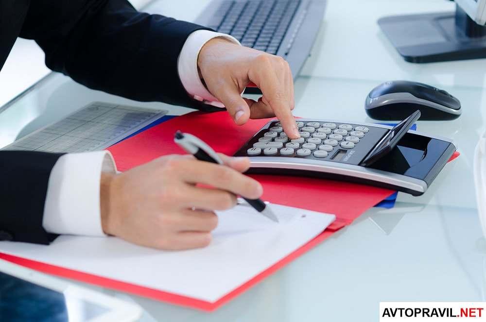 Мужчина считающий размер налога на калькуляторе