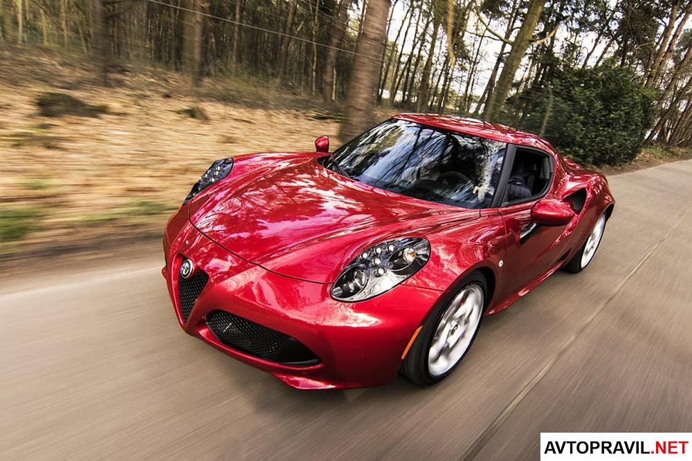 Красная спортивная машина едущая по дороге