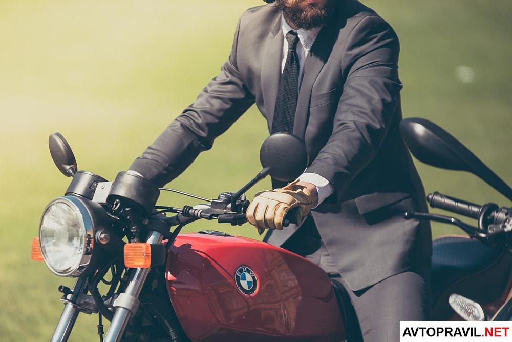 Мужчина в деловом костюме, который едет на мотоцикле