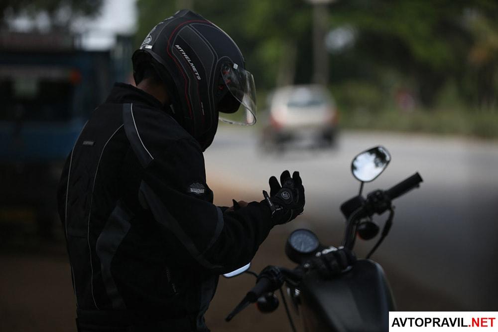 Мотоциклист в шлеме, застегивающий перчатку
