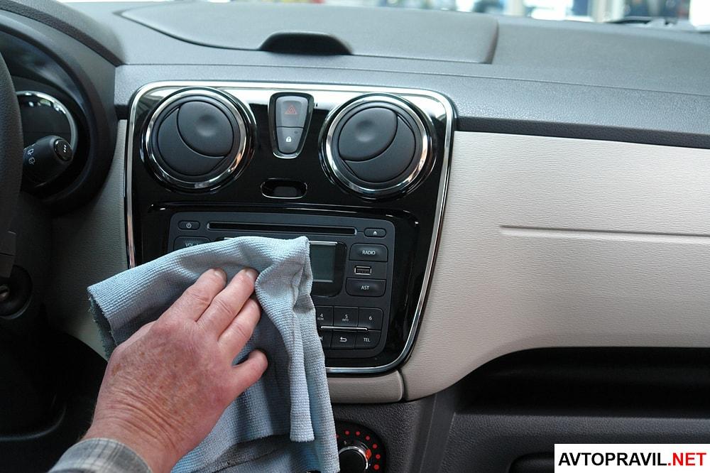 водитель протирает приборную панель автомобиля