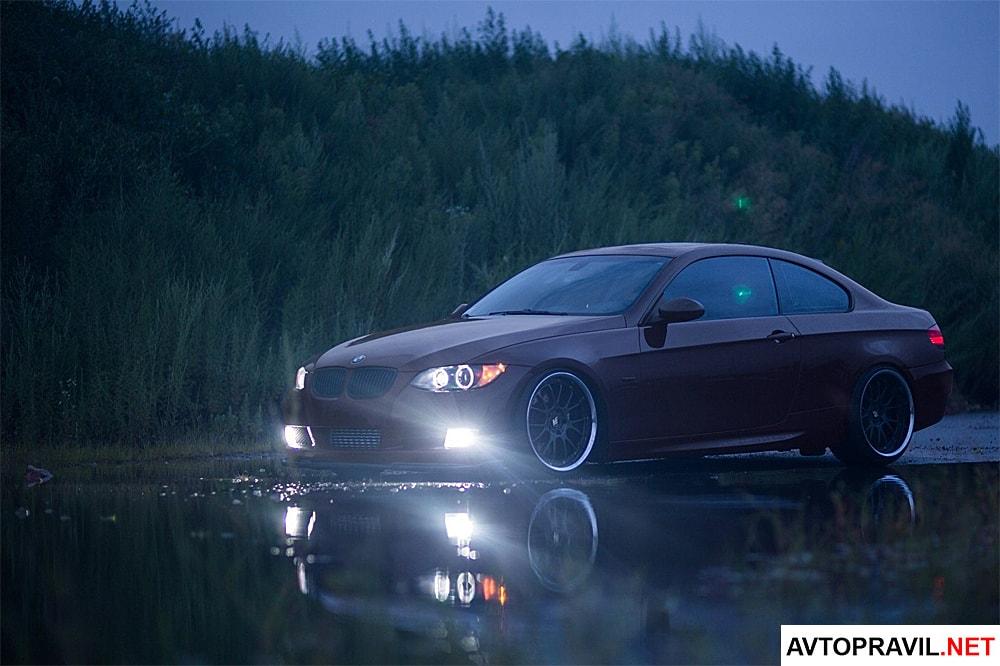 BMW едет с включенными фарами по мокрой дороге