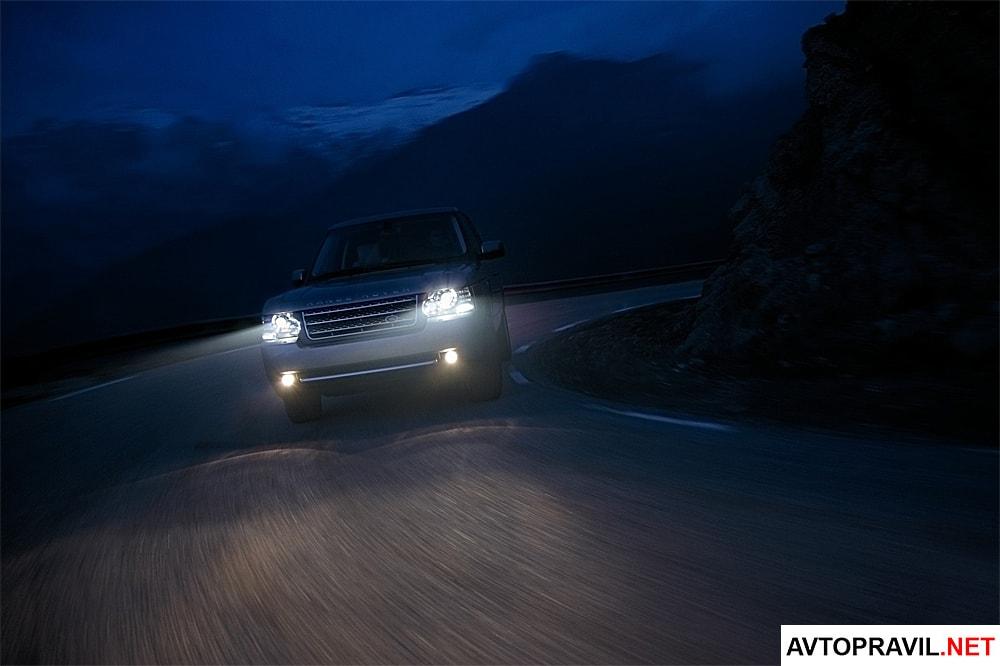 Range Rover с включенными фарами выезжающий из-за поворота