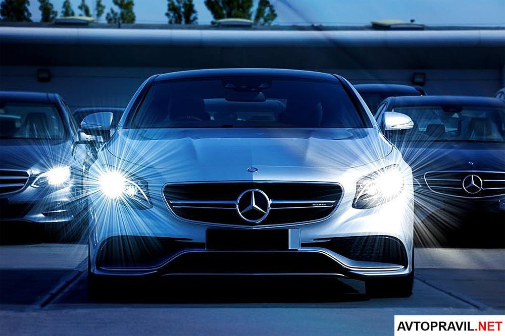 белый Mercedes с зажженными фарами