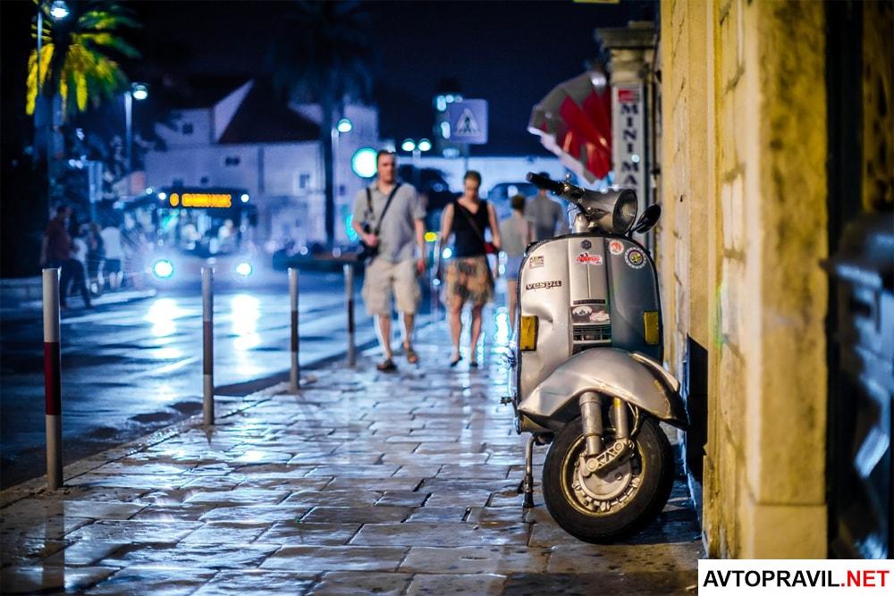 Припаркованный на тротуаре скутер