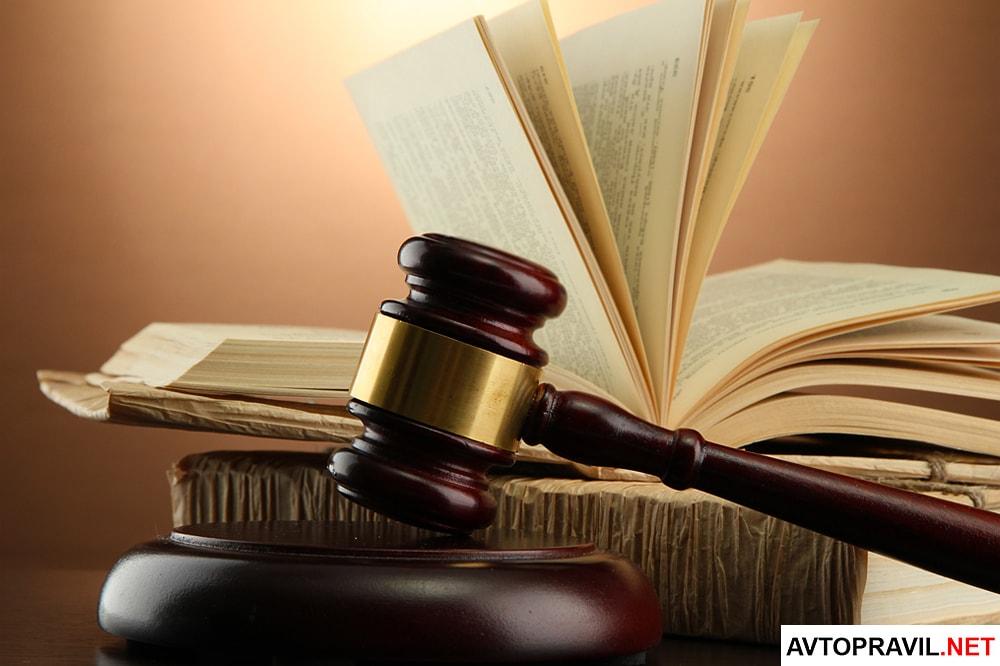 Судейский молоток и отрытая книга, лежащая на столе