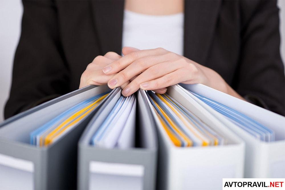 Женщина положившая руки на папки с документами