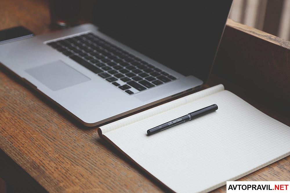 Блокнот и ручка, лежащие рядом с ноутбуком