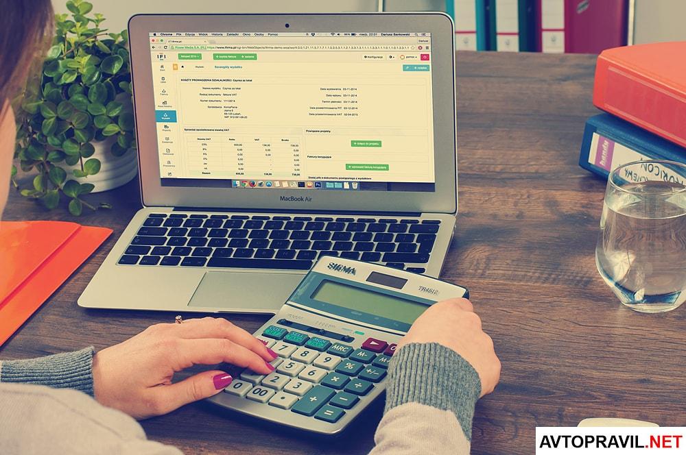 Девушка делает расчеты на калькуляторе