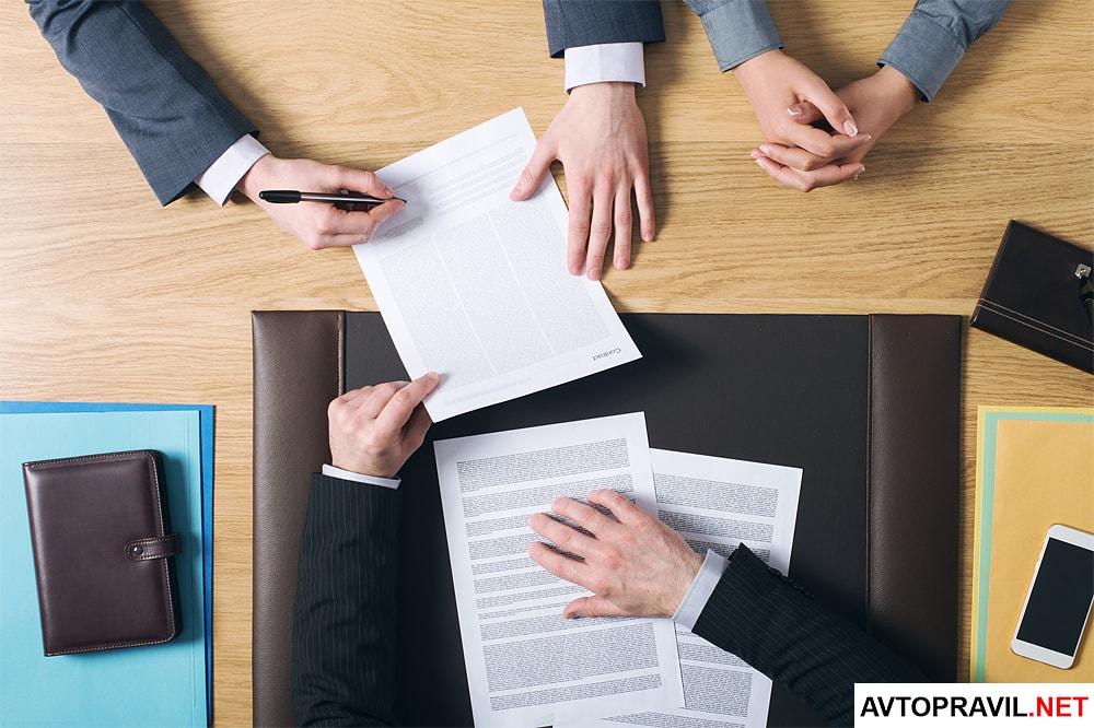 Люди, сидящие за столом и подписывающие документы