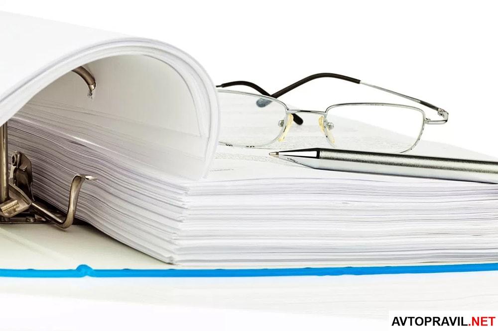 Папка с документами, очки и ручка