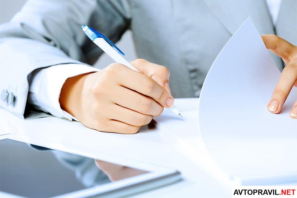 Женщина в деловом костюме, работающая с документами