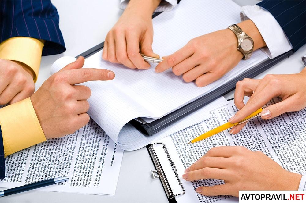 Три человека в деловых костюмах, работающие с документами