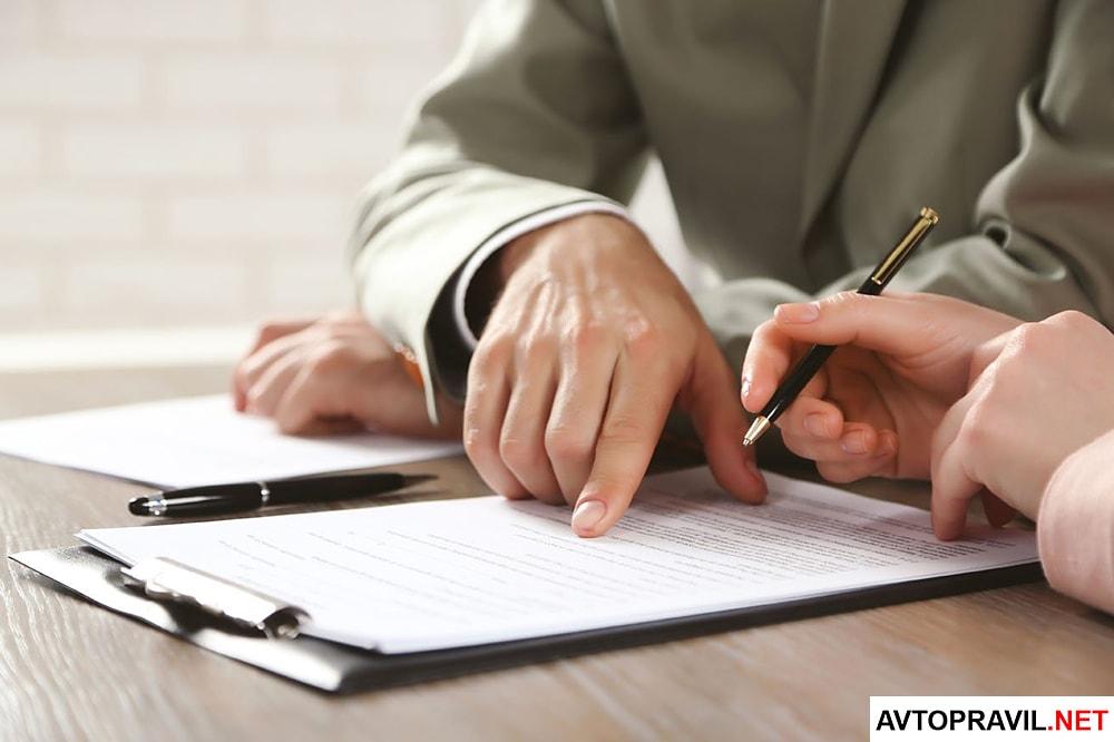 Два человека, подписывающие договор