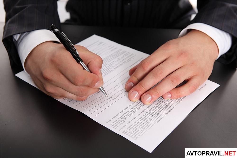 Мужчина в деловом костюме, заполняющий документы