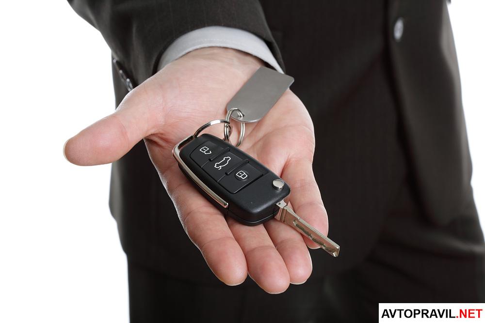 мужчина в деловом костюме с ключами от авто в руке