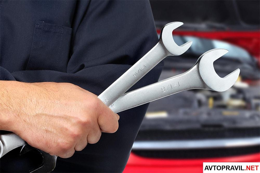 Механик, держащий в руках гаечные ключи