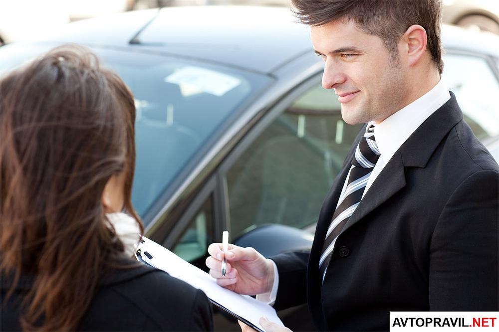 Мужчина и женщина с документами, стоящие возле автомобиля