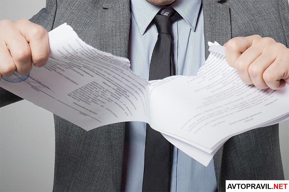 Мужчина рвущий документы