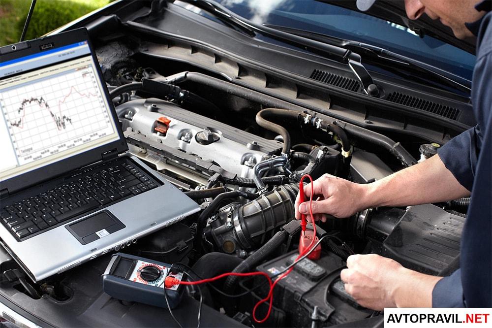 Мужчина проводящий диагностику автомобиля