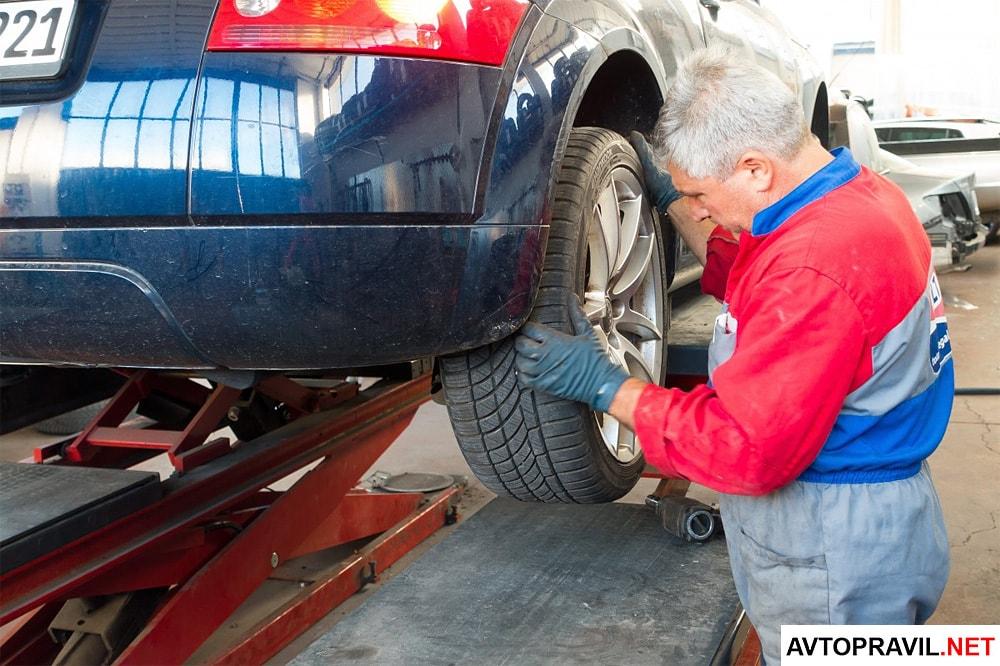 Механик осматривающий колеса автомобиля