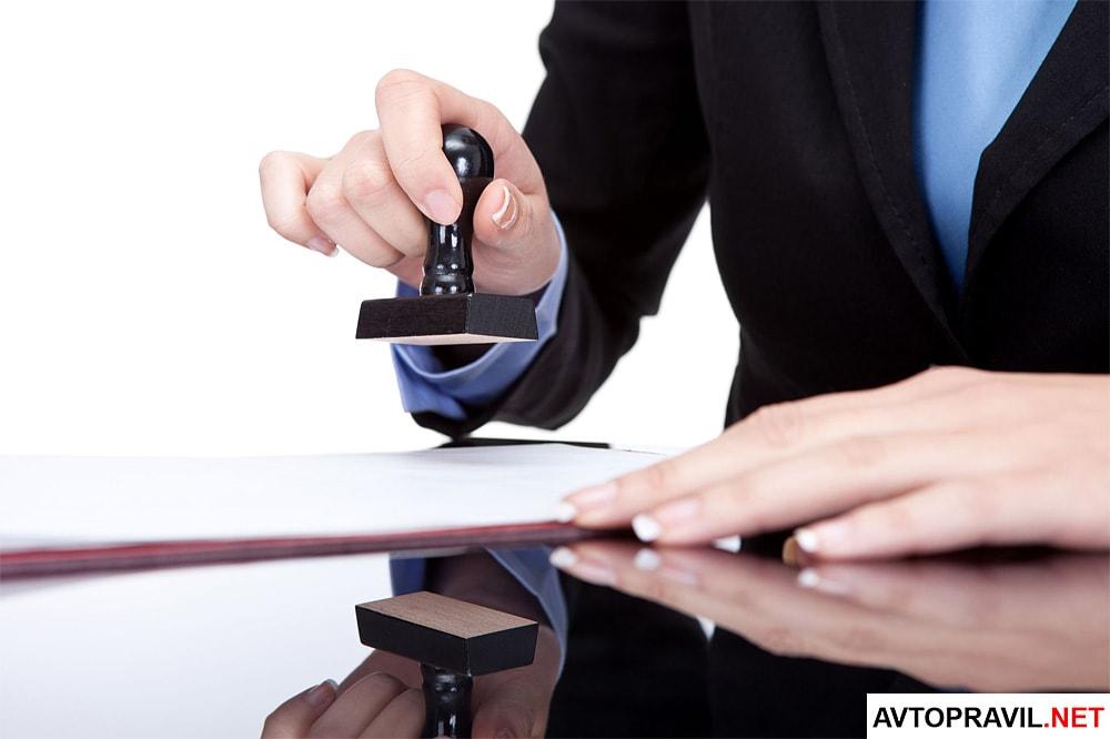 Женщина, которая ставит печать на документах