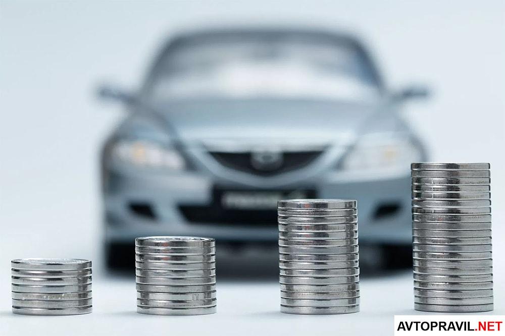 Стопки монет стоящие на фоне автомобиля