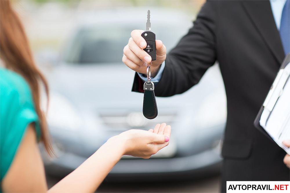 Мужчина передающий женщине ключи от автомобиля