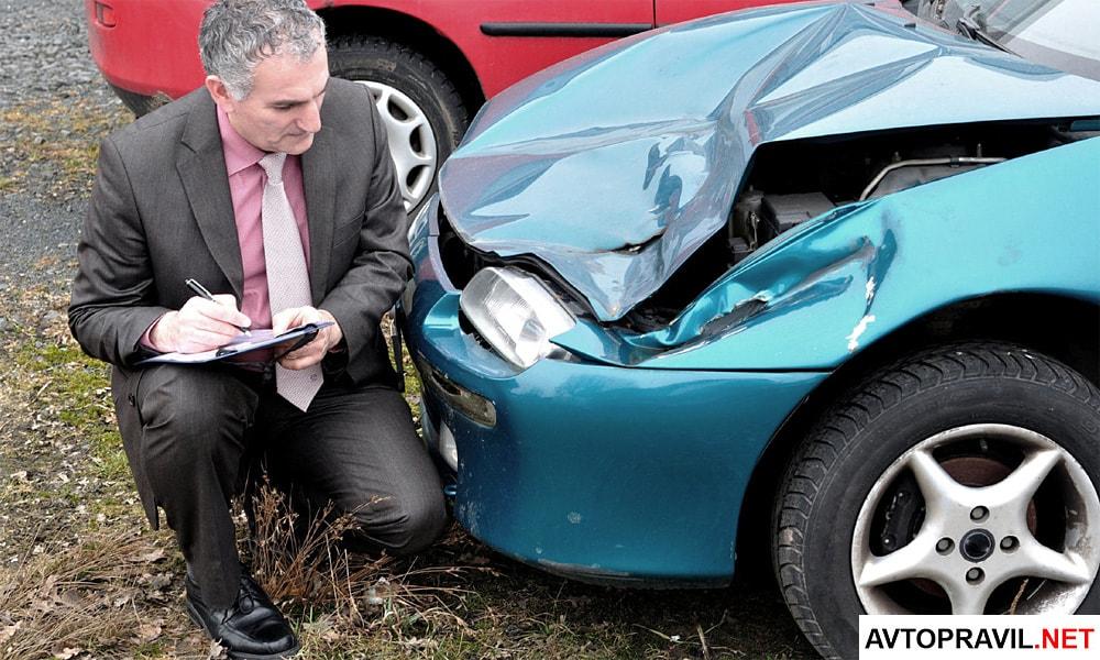 Мужчина, описывающий ущерб, нанесенный автомобилю