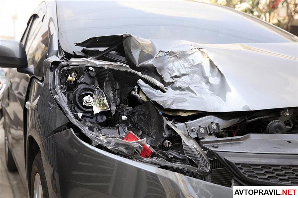 Разбитая фара и капот автомобиля