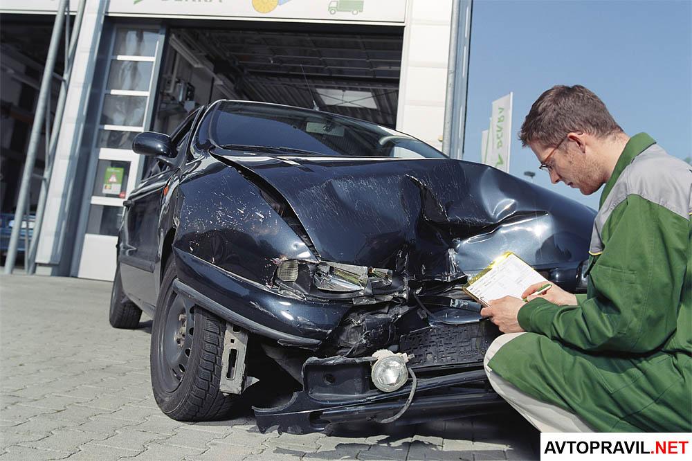 Эксперт, осматривающий авто и заполняющий документы