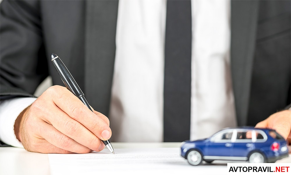 Мужчина заполняющий документы и игрушечный автомобиль стоящий на столе