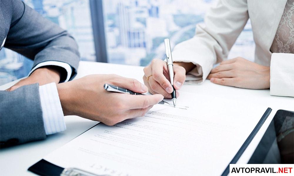 Два человека сидящих за столом и заполняющих документы