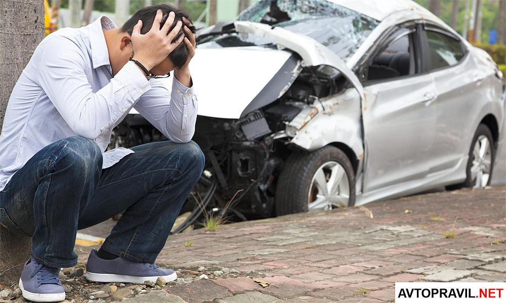 виновник аварии возле разбитой машины