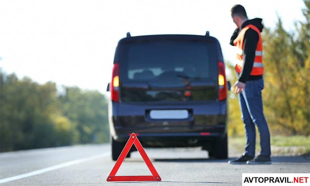 Аварийный треугольник и авария на дороге на заднем плане