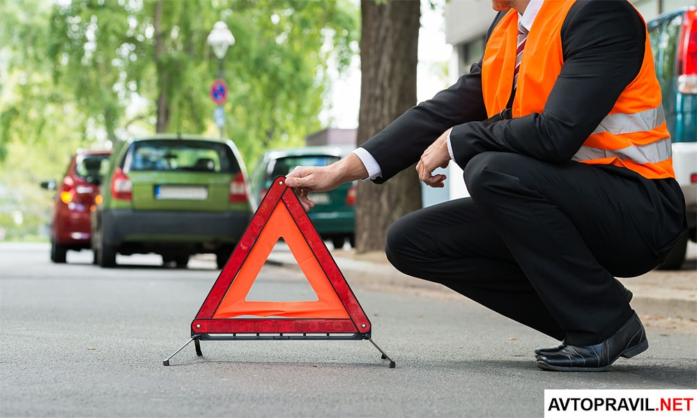 Человек выставляющий треугольник на дороге